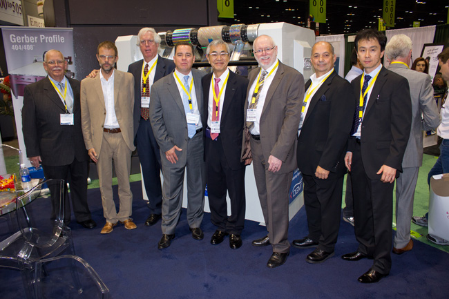 The DGM team in front of the Foildex Cold Foil Indexer at the Print 13 Trade Show in Chicago, IL