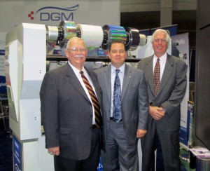 Paul Peyrebrune, Michael DeBard, and Dan Quenzer of Diversified Graphic Machinery at Print 13 in front of Foildex Cold Foil Indexing Unit